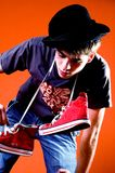 Drunk and Sick. Young man or teenage boy against orange background, red hightop sneakers around neck, hat tipped crooked, leaning and attempting to balance stock photography