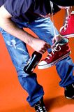 Drunk, Sick. Young man bending over with red hightop sneakers slung around neck, and holding beer bottle, wearing blue jeans stock photo