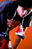 Drunk and Sick. Young man or teenager with red hightop shoes around neck with beer bottle stuck in one of the shoes, bending over royalty free stock photos