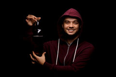 Drunk student on a black background. A boozed, pretty guy showing a bottle of alcoholic drink. Student party concept. A smiling student showing a full bottle of Royalty Free Stock Image