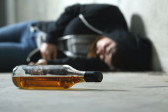 Drunk teenager on the floor. In a dark and sad place and an alcohol bottle in the foreground Stock Images