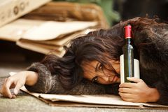 Drunk tramp woman. Holding bottle of wine and lying on pavemant Stock Photo
