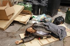 Drunk tramp woman in trash. Drunk tramp woman lying on cardboard in city trash area Royalty Free Stock Photography