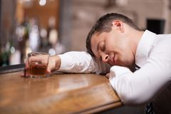 Drunk and unconscious businessman lying on counter. Royalty Free Stock Image