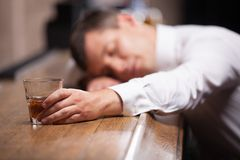 Drunk and unconscious guy lying on counter. Royalty Free Stock Photo