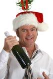 Drunk Under Mistletoe. A drunk man under the mistletoe holding a bottle of champagne Royalty Free Stock Photography