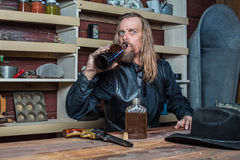 Drunk Western Man at Table. Drunk Western Man Looks Towards You as he Sits at Table Stock Image