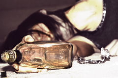 Drunk woman. Lying on the floor, bottle of alcohol in the hand - retro scene Stock Image