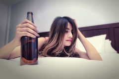 Drunk woman on the bed with bottle royalty free stock images