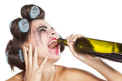 Drunk woman with curlers. Crying drunk young woman with curlers drinking wine from a bottle royalty free stock image