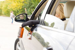 Drunk woman driver about to hit a pedestrian. Leaning to look out of the side window as she dangles her bottle of alcohol outdoors and taking her eyes off the Stock Images