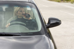 Drunk woman driving and drinking Royalty Free Stock Photos