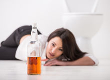 Drunk woman. Is lying on toilet floor with bottle of alcohol Royalty Free Stock Image