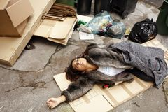 Drunk woman lying in trash stock photos