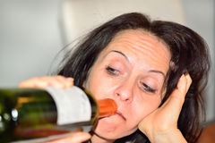 Drunk woman with red wine bottle Stock Images