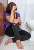 Drunk woman sitting in the bathroom Royalty Free Stock Photography
