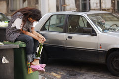 Drunk woman sitting on bin Stock Image