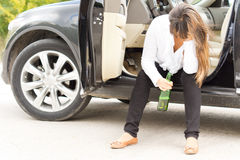 Drunk woman sitting in the door of her car Stock Image