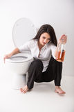 Drunk woman. Is sitting on the toilet floor and is holding a whisky bottle Royalty Free Stock Photography