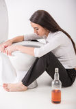 Drunk woman. Is sitting on the toilet floor and is holding a whisky bottle Stock Photos