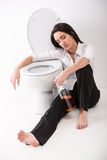 Drunk woman. Is sitting on the toilet floor and is holding a whisky bottle Royalty Free Stock Photos
