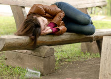 Drunk woman sleeping it off on a wooden bench Stock Images