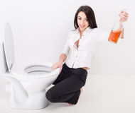 Drunk woman. Top view of drunk woman is sitting on the toilet floor and is holding a whisky bottle Stock Photos