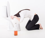 Drunk woman. Vomiting on a toilet bowl. Bottle with alcohol on the floor Stock Image