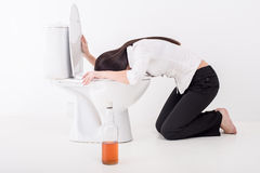 Drunk woman. Vomiting on a toilet bowl. Bottle with alcohol on the floor Royalty Free Stock Photo