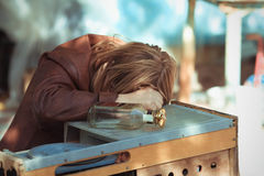 The drunk woman who fell asleep on a table Royalty Free Stock Images