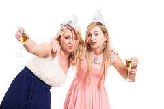 Drunk women celebrate. Two drunk women celebrate with alcohol, isolated on white background Royalty Free Stock Photo