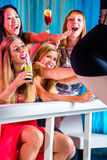 Drunk women with fancy cocktails in strip club. Friends watching striptease in strip club grabbing at female stripper Stock Photos
