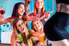 Drunk women with fancy cocktails in strip club. Friends watching striptease in strip club grabbing at female stripper Stock Photo