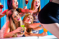 Drunk women with fancy cocktails in strip club. Friends watching striptease in strip club grabbing at female stripper Stock Image