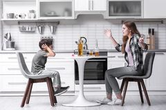 Drunk woman yelling at her son. Drunk women yelling at her son in kitchen Royalty Free Stock Photo