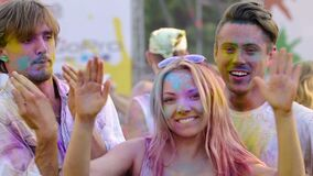Drunk young friends covered in colorful paint performing crazy dance at festival. Stock footage stock video footage
