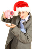 Drunk young man in Christmas hat with piggy bank Royalty Free Stock Photography