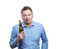 Drunk young man. Funny young drunk man holding a beer bottle. Studio shot on white background Royalty Free Stock Images