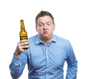 Drunk young man. Funny young drunk man holding a beer bottle. Studio shot on white background Stock Images