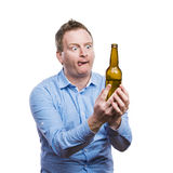 Drunk young man. Funny young drunk man holding a beer bottle. Studio shot on white background stock photography