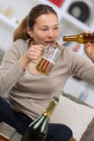 Drunk young on sofa with bottle beer in hand Royalty Free Stock Photography