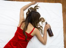 Drunk young topless woman sleeping on bed. With bottle of vine in hand Royalty Free Stock Photo