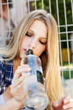 Drunk young woman with bottle of alcohol Stock Images