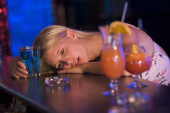 Drunk young woman resting head on bar counter stock photography