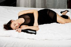 Drunk young woman sleeping on bed. Royalty Free Stock Photography
