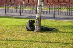 A drunkard lying on the grass wakes up. On a sunny afternoon Royalty Free Stock Photo