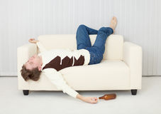 Drunkard sleeps on sofa in an amusing pose Stock Photos