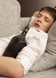 Drunkard. A young man with a drinking problem is relaxing Stock Photos