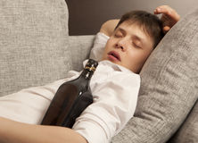 Drunkard. A young man with a drinking problem is relaxing Royalty Free Stock Photography