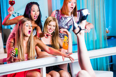 Drunken girls with fancy cocktails in strip club. Friends watching striptease in strip club grabbing at female stripper Stock Images